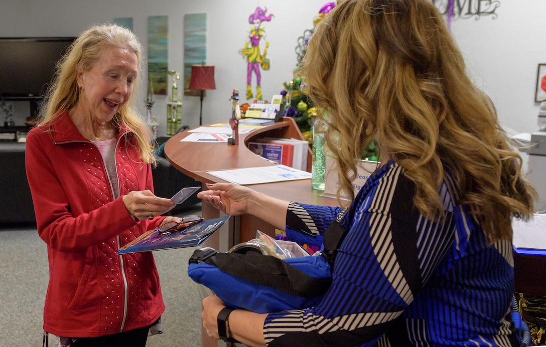 Holly Fisher, 81st Force Support Squadron Airman & Family Readiness Center community readiness specialist, presents Mary Buckley, daughter of U.S. Air Force Capt. Robert Gereer, with her Gold Star Family Member ID card inside the Sablich Center at Keesler Air Force Base, Mississippi, Feb. 15, 2019. Gereer served during the Korean War and was placed in a missing in action (MIA) status due to his remains not being found. As a surviving daughter of an MIA service member, Buckley is allowed to obtain an ID card for recognition and installation access so that she can attend events and access A&FRC referral services. (U.S. Air Force photo by Andre' Askew)