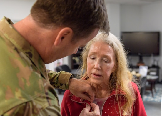 U.S. Air Force Col. Lance Burnett, 81st Training Wing vice commander, pins a Gold Star Family Member lapel pin on the collar of Mary Buckley, daughter of U.S. Air Force Capt. Robert Gereer, inside the Sablich Center at Keesler Air Force Base, Mississippi, Feb. 15, 2019. Gereer served during the Korean War and was placed in a missing in action (MIA) status due to his remains not being found. As a surviving daughter of an MIA service member, Buckley is allowed to obtain an ID card for recognition and installation access so that she can attend events and access A&FRC referral services. (U.S. Air Force photo by Andre' Askew)