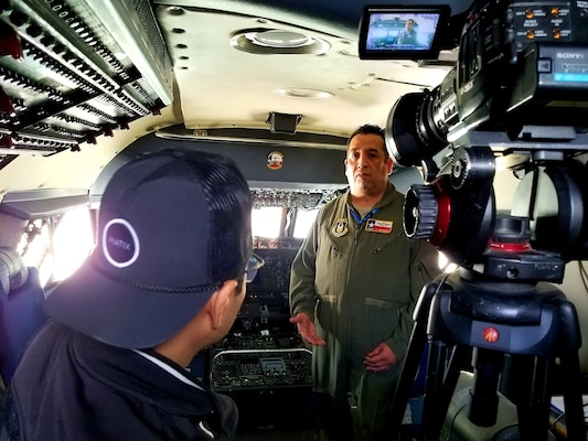 Senior Master Sgt. Alfonso Cervantes, 68th Airlift Squadron loadmaster, speaks with a local television station crew in both English and Spanish while in the cockpit of the 433rd Airlift Wing's C-5M Super Galaxy from Joint Base San Antonio-Lackland at the Laredo International Airport in Laredo, Texas Feb. 17. Cervantes, a Laredo J.W. Nixon High School graduate, was part of the aircrew that flew the aircraft to the Washington's Birthday Celebration Association Stars and Stripes Air Show Spectacular.