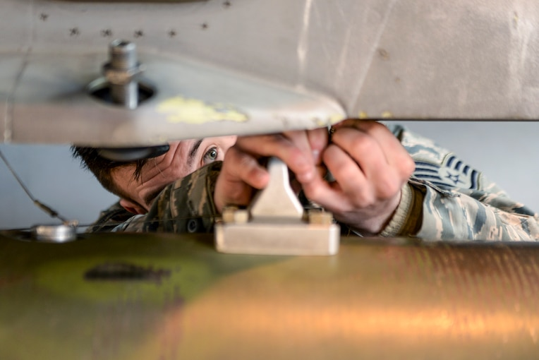 An airman's face is partially obscured between horizontal sections of metal and his hands as he does maintenance-type work.