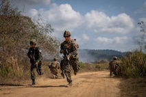 A  U.S. and Thai Marine run down a dirt road during a training exercise.