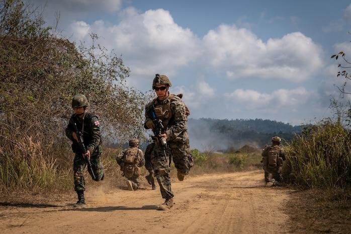 A  U.S. and Thai Marine run down a dirt road during a training exercise.