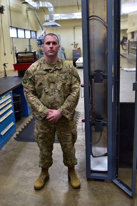 Airman stands next to his safety fixture.