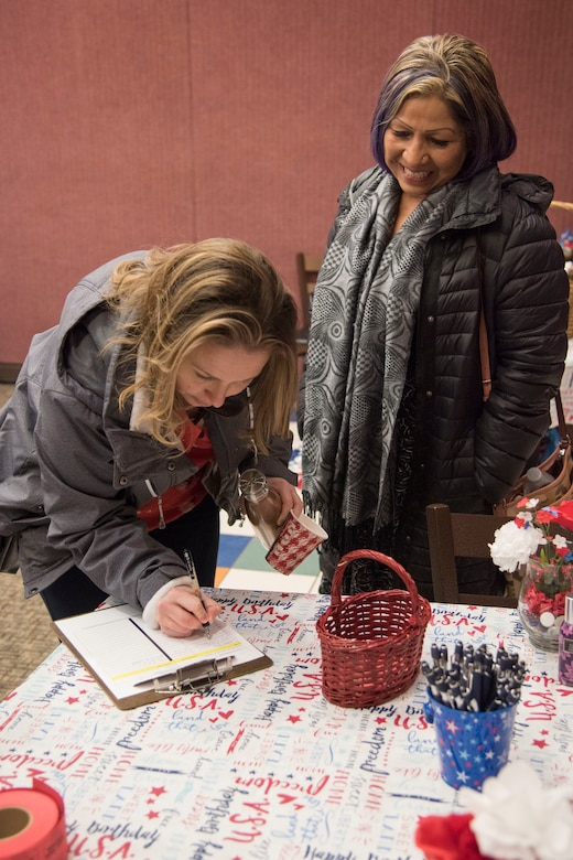 """Attendees sign in during a military spouse town hall and luncheon at Joint Base Elmendorf-Richardson, Alaska, Feb. 12, 2019. The Military and Family Readiness Center-hosted event had more than 120 attendees with the theme """"Taking Care of People."""""""
