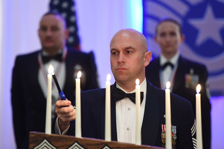 U.S. Air Force Chief Master Sgt. Shawn Andrews, 81st Security Forces Squadron manager, participates in a candle-lighting ceremony during the Chief Induction Ceremony inside the Bay Breeze Event Center at Keesler Air Force Base, Mississippi, Feb. 15, 2019. During the candle-lighting ceremony a candle is lit for each rank of the enlisted structure an Airmen wears on their way to the rank of chief master sergeant. Five Keesler Airmen earned their chief master sergeant stripe during the 2019 promotion release. Air Force officials selected 479 senior master sergeants for promotion to chief master sergeant out of 2,241 eligible for a selection rate of 21.37 percent. Chief master sergeants make up one percent of the Air Force enlisted force. (U.S. Air Force photo by Kemberly Groue)