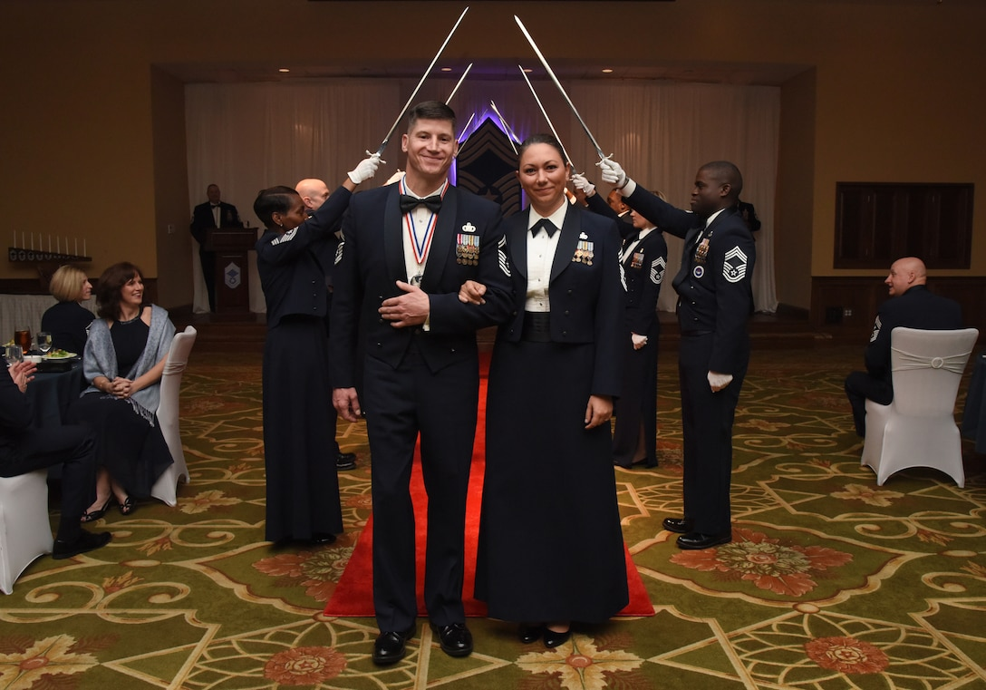 U.S. Air Force Senior Master Sgt. Kevin Lambert, 81st Security Forces Squadron operations superintendent, and his wife, Chief Master Sgt. Sevin Balkuvvar, 96th Logistics Readiness Squadron materiel management flight superintendent, Eglin Air Force Base, Florida, pose for a photo after walking under an archway of sabers held by Keesler's Chief Master Sgts. during the Chief Induction Ceremony inside the Bay Breeze Event Center at Keesler Air Force Base, Mississippi, Feb. 15, 2019. Five Keesler Airmen earned their chief master sergeant stripe during the 2019 promotion release. Air Force officials selected 479 senior master sergeants for promotion to chief master sergeant out of 2,241 eligible for a selection rate of 21.37 percent. Chief master sergeants make up one percent of the Air Force enlisted force. (U.S. Air Force photo by Kemberly Groue)