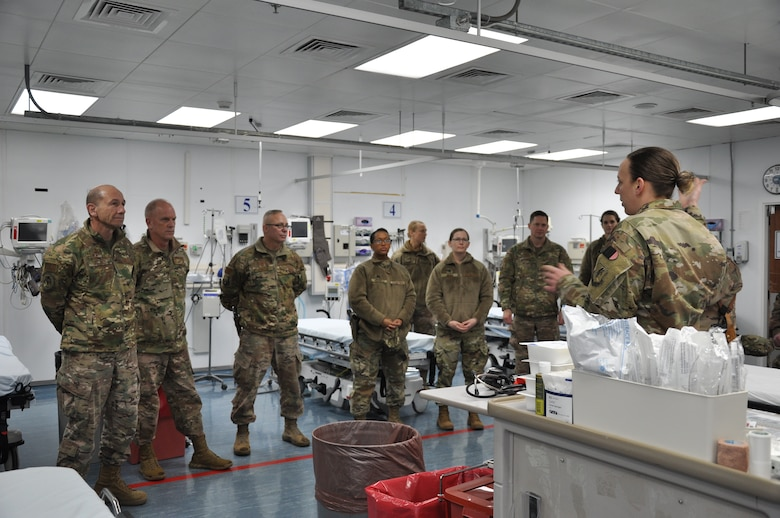 Airmen from the 455th Expeditionary Medical Group brief Gen. Mike Holmes, commander of Air Combat Command, and Chief Master Sgt. Frank H. Batten III, ACC command chief master sergeant, about patient care at Bagram Airfield, Afghanistan, Feb. 13, 2019.