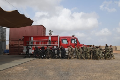 The 870th Air Expeditionary Squadron fire department and military community took part in a decades-old tradition and pushed a fire truck into its new home during a ceremony here Feb. 8.