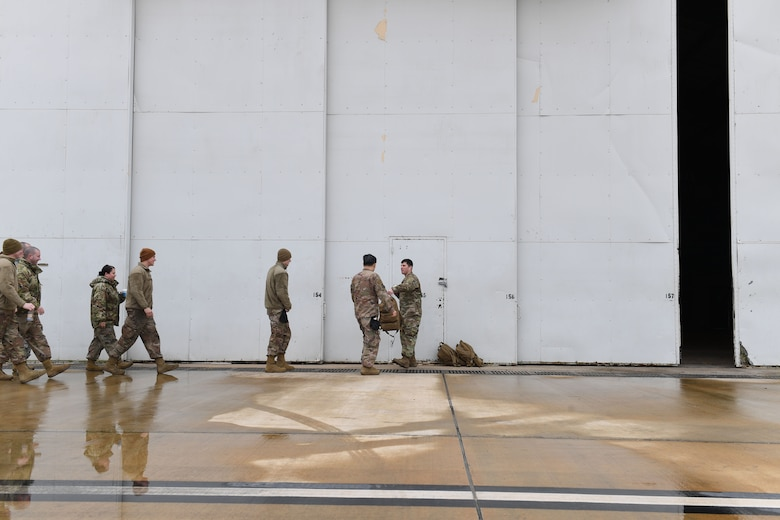 A group of people walk towards a doorway.