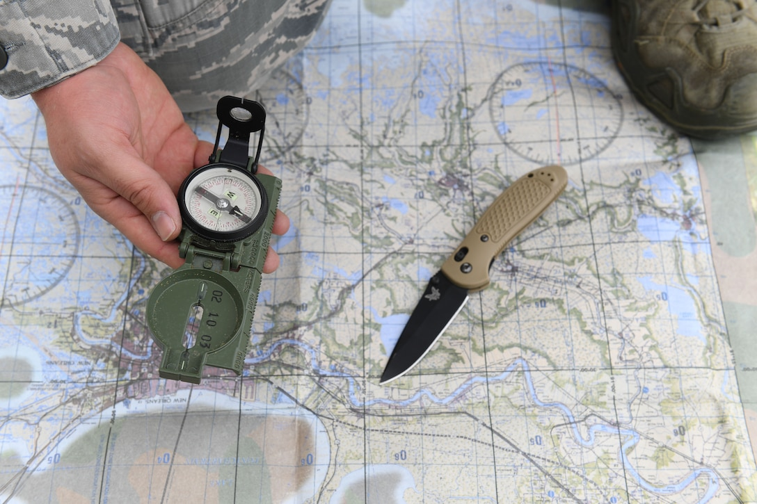 A man holds a compass over a map.