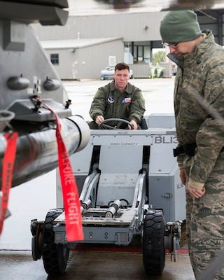 1st Lt. Wesley Kilmain ( left), an F-16 Fighting Falcon student pilot, drives a MJ-1 lift truck as Tech. Sgt. Brian Green, 149th Fighter Wing load standardization crewmember, observes weapons loading during training at Joint Base San Antonio-Lackland Feb. 9.