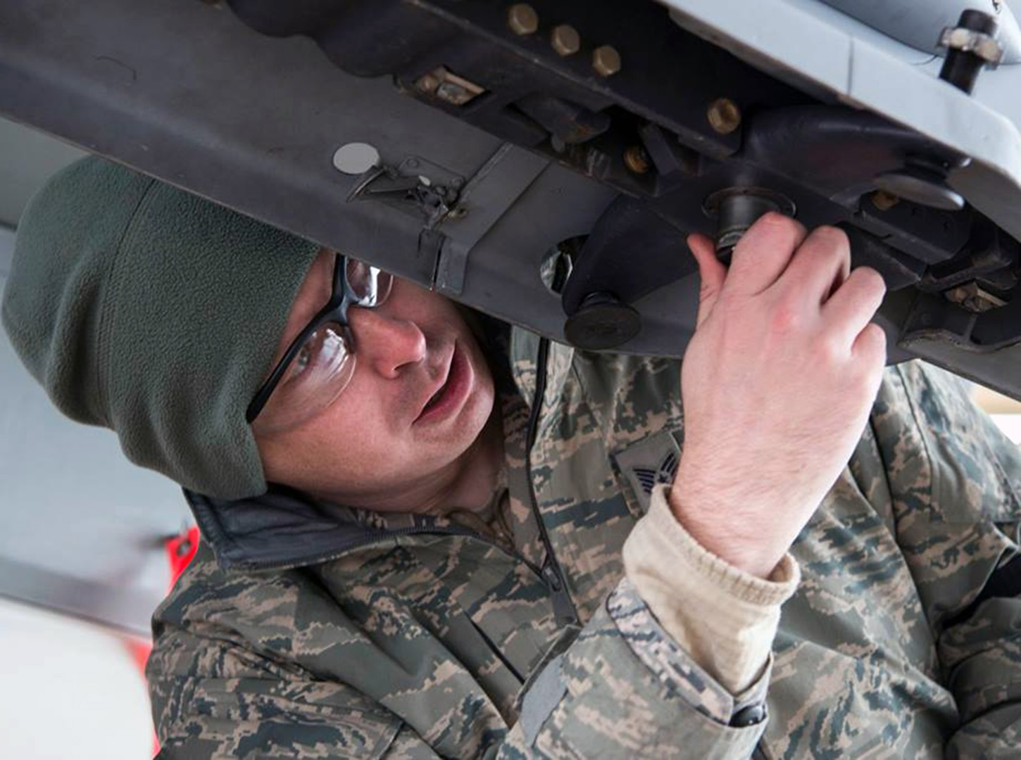 Tech. Sgt. Brian Green, a 149th Fighter Wing load standardization crewmember, adjusts the underside of an F-16 Fighting Falcon wing during weapons training at Joint Base San Antonio-Lackland Feb. 9.