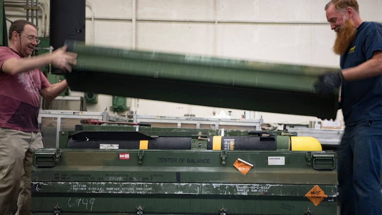 Naval Air Systems Command munitions inspectors Jack Sigler, left, and Greg Groover unseal an AGM-114 HELLFIRE missile from a storage container Feb. 5, 2019, at the Naval Weapons Station in Goose Creek, S.C.