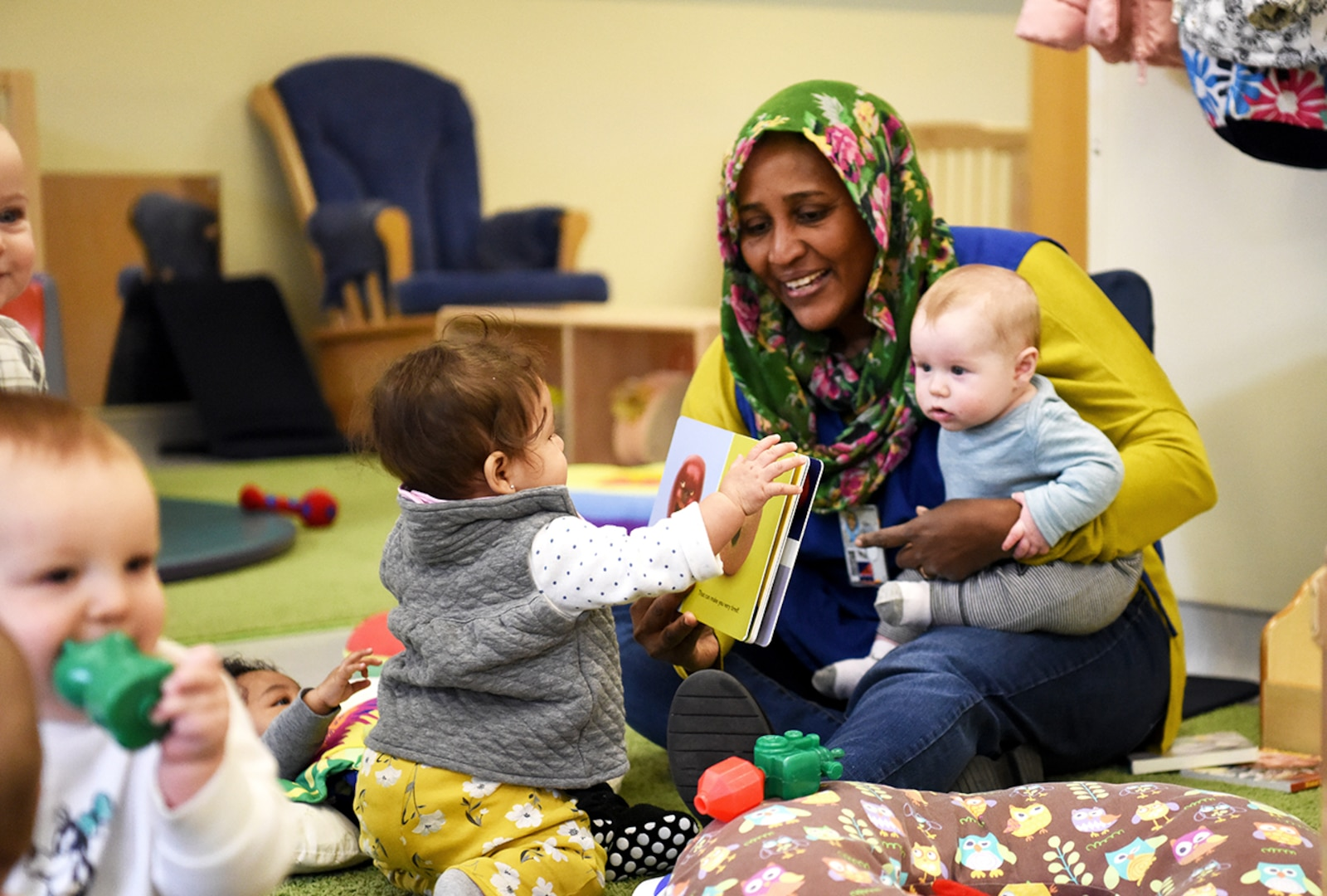 Emtithal Sulieman reads a book with colorful illustrations to help develop babies' voice and image-recognition skills at DLA's Fort Belvoir, Virginia, Child Development Center.
