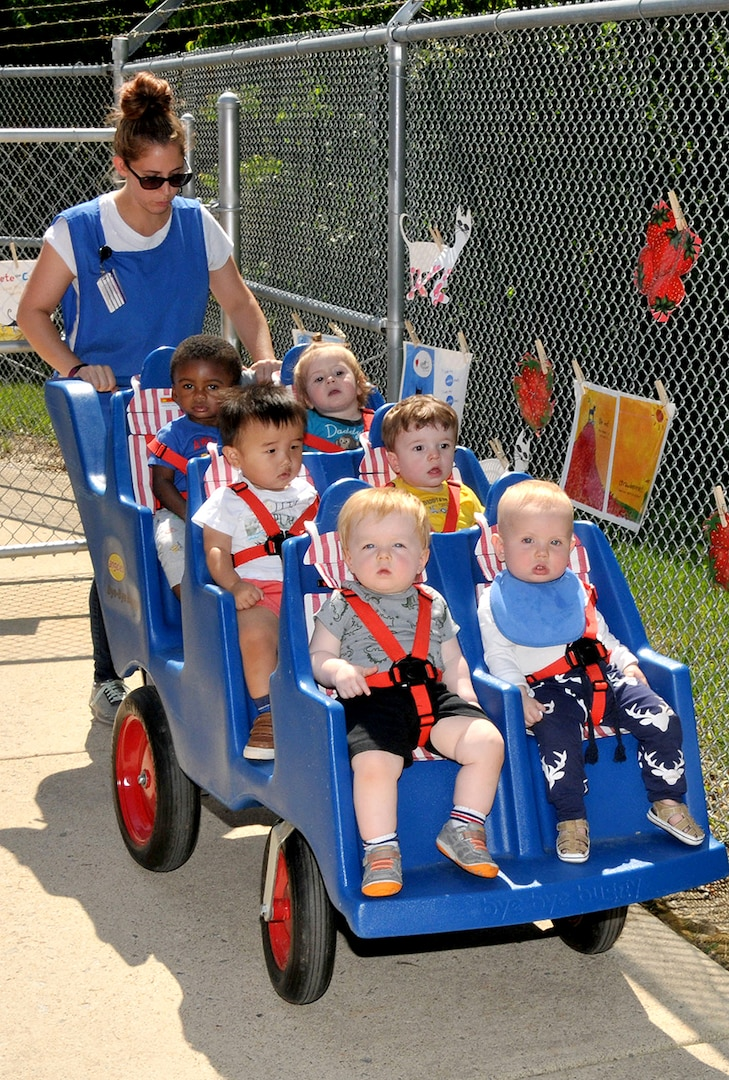 """Katelyn Brusso, a staff member at DLA's Fort Belvoir, Virginia, Child Development Center, takes children on a short journey during a Book Walk featuring """"Pete the Cat and His Very White Shoes"""" in May 2018."""