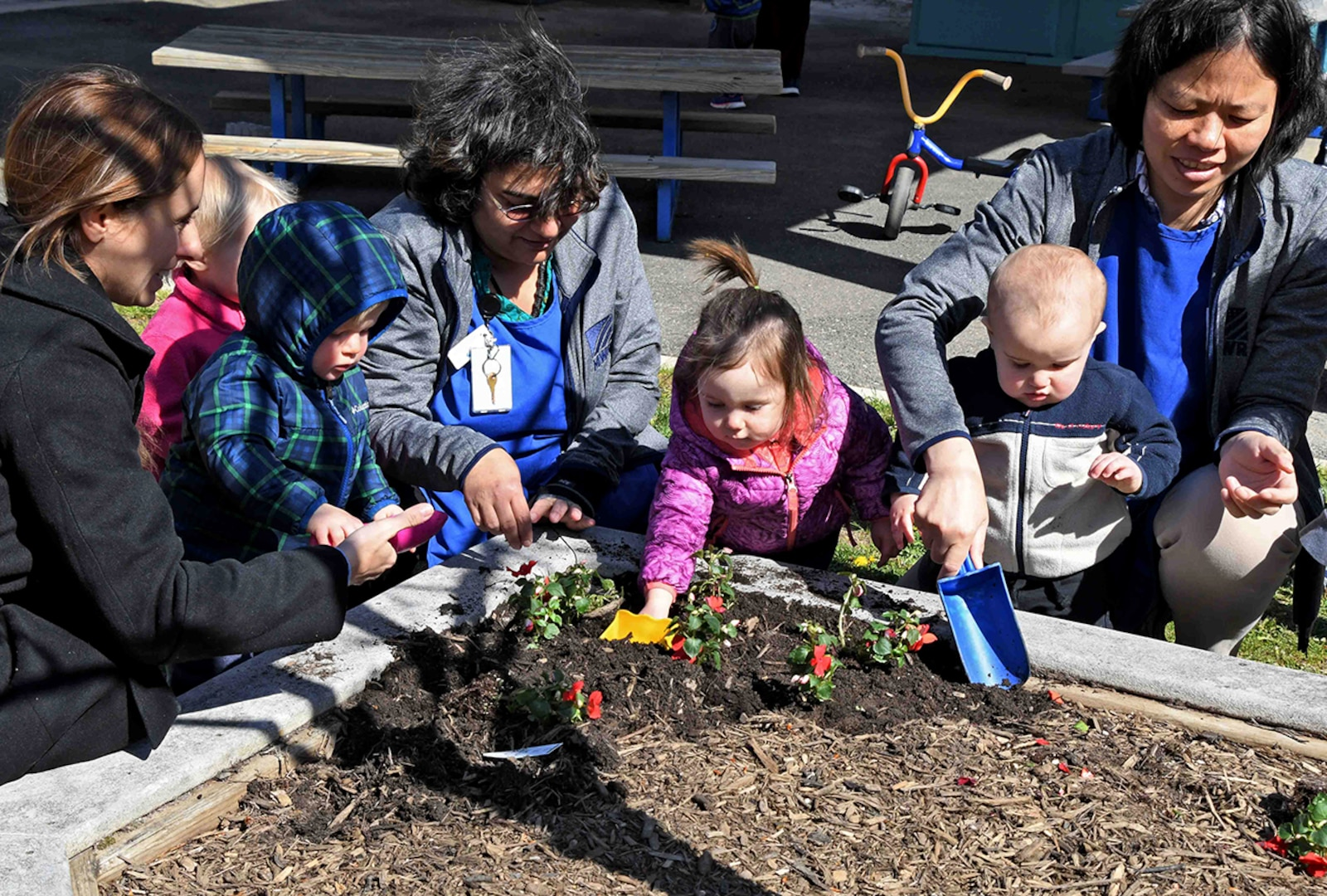 Child Development Center staff, parents and children plant flowers in honor of Earth Day in April 2018.