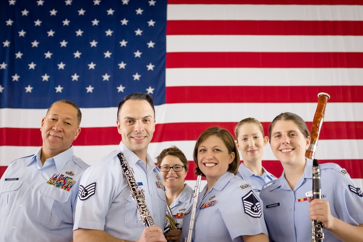 Image of woodwind players standing in uniform in front of the American flag