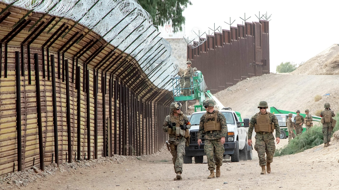Marines with the 7th Engineer Support Battalion, Special Purpose Marine Air-Ground Task Force 7, walk along the California-Mexico border at the Andrade Point of Entry in Winterhaven, California. U.S. Northern Command provided support to the Department of Homeland Security and U.S. Customs and Border Protection to secure the southwest border of the United States.