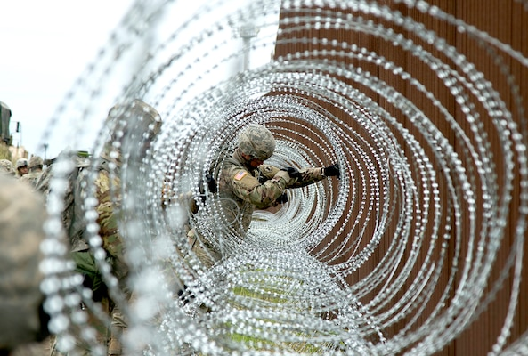 Army Pvt. William Crowder of the 887th Engineer Support Company applies concertina wire near Brownsville, Texas.