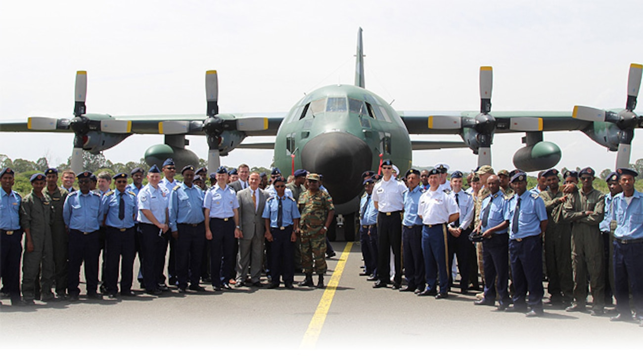 Members of the US and Ethiopian Air Force pose in front of a C-130 Hercules plane.