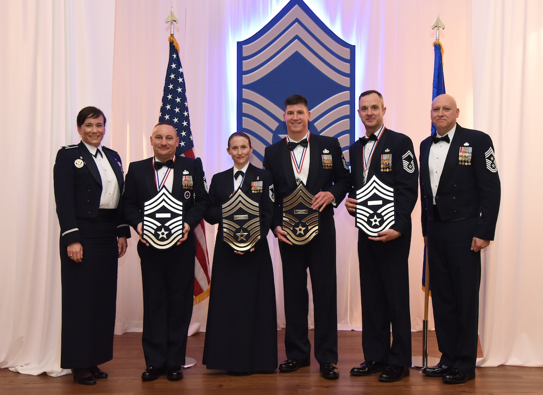 Leadership from the 81st Training Wing poses with Keesler's newest chief master sergeants holding plaques displaying their line numbers during the Chief Induction Ceremony inside the Bay Breeze Event Center at Keesler Air Force Base, Mississippi, Feb. 15, 2019. Five Keesler Airmen earned their chief master sergeant stripe during the 2019 promotion release. Air Force officials selected 479 senior master sergeants for promotion to chief master sergeant out of 2,241 eligible for a selection rate of 21.37 percent. Chief master sergeants make up one percent of the Air Force enlisted force. (U.S. Air Force photo by Kemberly Groue)