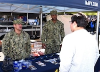 Chief Petty Officer Juan Ramirez (left) and Petty Officer 1st Class Vincent Barnes (right) of Navy Recruiting District San Antonio speak with an attendee at the San Antonio Stock Show and Rodeo.