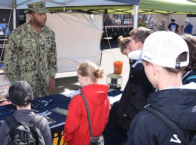 Petty Officer 1st Class Vincent Barnes of Navy Recruiting District San Antonio, speaks with attendees at the San Antonio Stock Show and Rodeo.