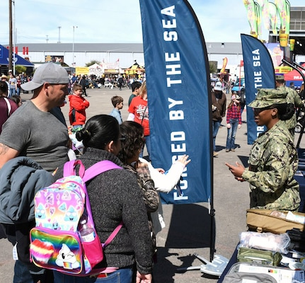Chief Petty Officer Calvanna Major, from the Navy Medical Training Support Center, speaks with a family attending the San Antonio Stock Show and Rodeo.