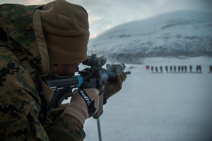 Marine aiming a rifle at targets