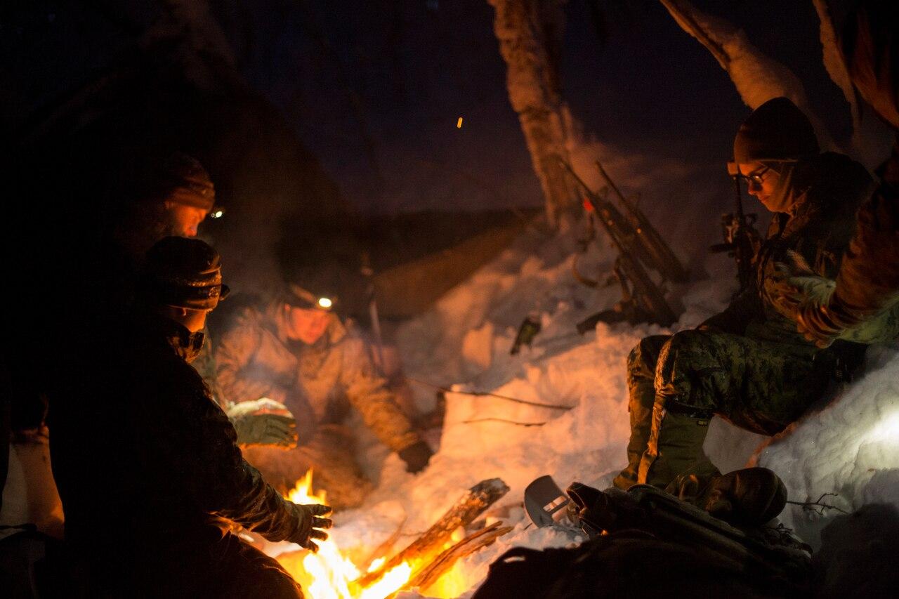 Marine huddle around campfire
