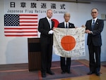 U.S. Air Force Senior Master Sgt. William Armstrong, 8th Logistics Readiness Squadron deployment and distribution flight superintendent, (left), hands a Japanese flag to Michio Miki (middle) and Hideo Ito, Masashi Ito's nephews, during a flag return ceremony in Takasaki, Japan, Feb. 14, 2019. Armstrong's grandfather acquired Miki and Ito's uncle's flag during World War II.