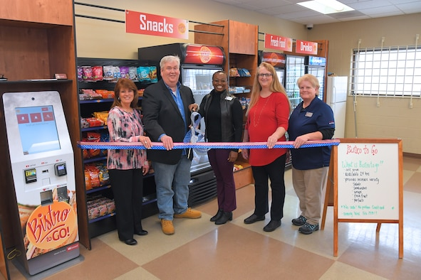 "(Left to right) Valerie Carr, 309th Sofware Maintenance Group flight director, Enos Cummings, 309th SMXG engineering supervisor, Melanie White, AAFES general manager, Susan Heaps, AAFES business manager, and Marjorie Rosier, AAFES vendor technician, cut a ribbon during a ceremony Feb. 14, 2019, celebrating the opening of a new ""Bistro to Go"" located in building 1515 at Hill Air Force Base, Utah. The self-serve store offers a variety of food and drinks for 309th SMXG employees who work in the facility. (U.S. Air Force photo by Todd Cromar)"