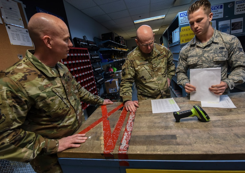 Chief Master Sgt. Daniel C. Simpson, left, 18th Air Force command chief master sergeant, Maj. Gen. Sam C. Barrett, center, 18th Air Force commander, and Senior Airman Jacob Wuerth, right, 437th Aircraft Maintenance Squadron aerospace maintenance apprentice, discuss the way Wuerth's unit has streamlined the tool tracking process Feb. 13, 2019, at Joint Base Charleston, S.C.