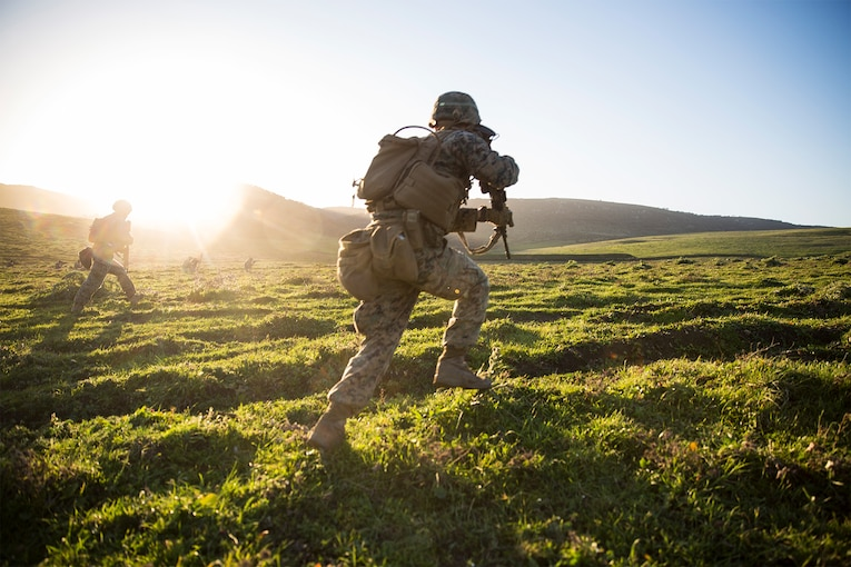 Marines run toward a target during training.