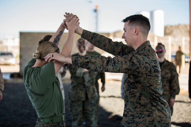 "U.S. Marines assigned to Marine Aviation Logistics Squadron (MALS) 13 and their spouses participate in Jane Wayne Day at Marine Corps Air Station (MCAS) Yuma Jan. 25, 2019. Jane Wayne Day consisted of applying camouflage paint, getting some ""drill instructor time"", conducting a modified combat fitness test (CFT), going through the Obstacle Course, learning a few Marine Corps Martial Arts Program (MCMAP) techniques, and shooting the Beretta M9 Pistol. Jane Wayne Day is designed to give the spouses a little insight on some of the things their Marine does while having fun. (U.S. Marine Corps photo by Cpl. Sabrina Candiaflores)"