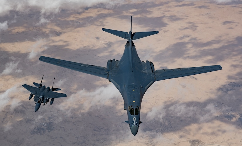 A U.S. Air Force B-1B Lancer bomber and F-15E Strike Eagle fly in formation during Joint Air Defense Exercise 19-01, Feb. 19, 2019. The aircraft participated with regional partners to test objective-based command and control actions during the exercise. JADEX is an opportunity to test and improve combined air and missile defense capabilities and ensure Joint Coalition partners are prepared to defend against external threats with a variety of capabilities and assets. (U.S. Air Force photo by Staff Sgt. Clayton Cupit)