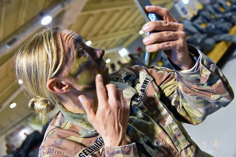 A soldier applies face paint while looking in a hand mirror.
