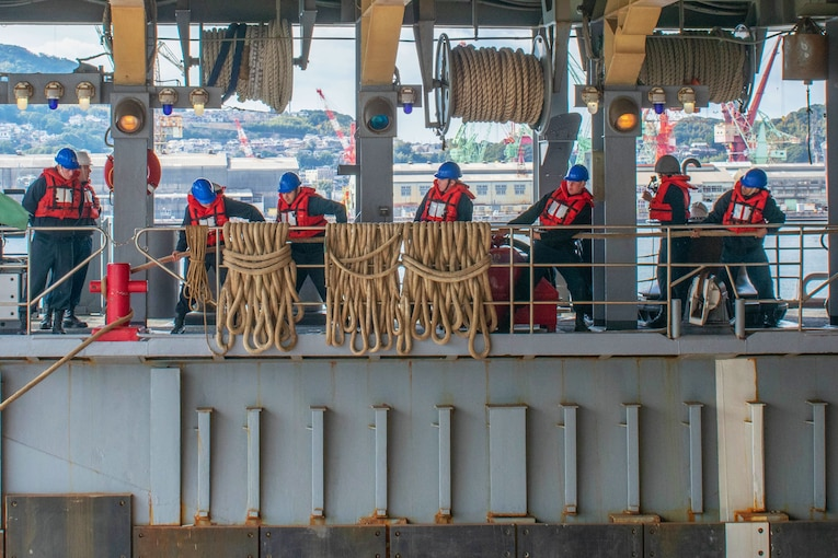 Several sailors on a ship pull ropes.
