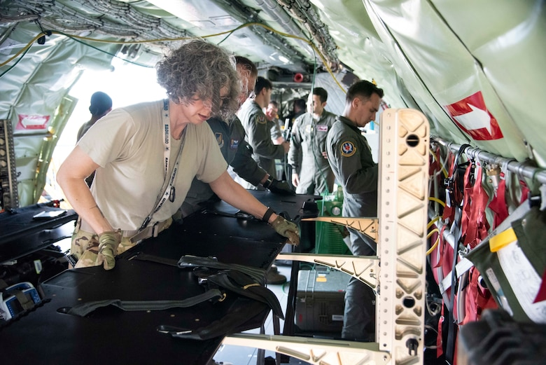 U.S. Air Force Capt. Tracy Minke, 18th Aeromedical Evacuation Squadron flight nurse, sets-up a specialized litter rack on a 384th Air Refueling Squadron KC-135 Stratotanker during an AE exercise near Kadena Air Base, Japan, Feb. 19, 2019. AE teams use specialized gear to safely secure critical care patients and maximize space on an aircraft, convert aircraft power to their medical equipment, and protect medics and patients in the event of an in-flight emergency. (U.S. Air Force photo by Senior Airman Ryan Lackey)