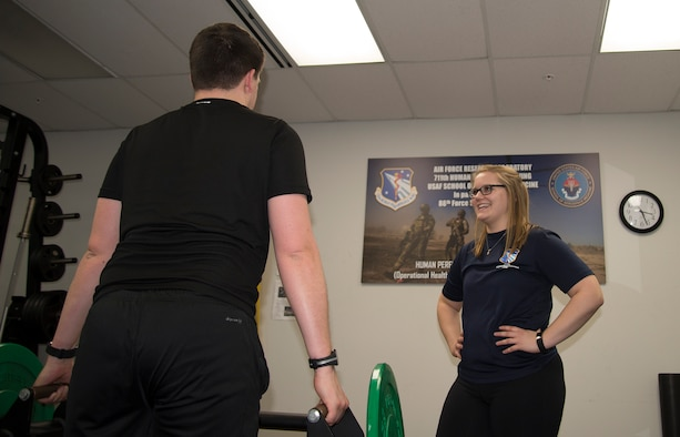 Hannah Kohne, a contractor at the 711th Human Performance Wing, takes Staff Sgt. Alan Gagnon through an exercise routine as a part of the Function Bridge Fitness Study at Wright Patterson Air Force Base, Feb. 14, 2019.