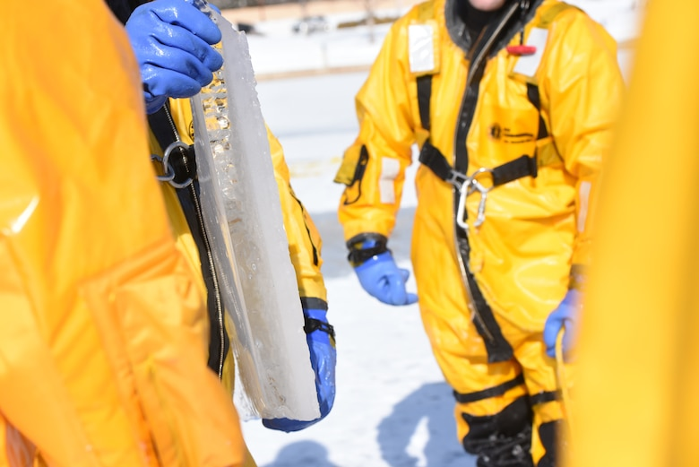 Brian Povandra, a Rapid City Fire Department ice rescue instructor, holds up a fragment of ice from the lake to show Airmen from the 28th Civil Engineer Squadron Fire Protection Flight the thickness of the ice they were standing on at CanyonLake in Rapid City, S.D., Feb. 12, 2019. The thickness of the ice on the lake that day ranged from 2 to 10 inches. (U.S. Air Force photo by Senior Airman Michella Stowers)