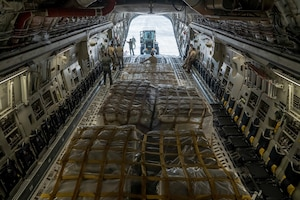 Airmen work to load pallets on a plane