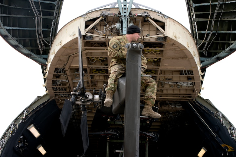 Airmen, Soldiers and personnel prepare to load Apache Helicopters into a C-5 Galaxy