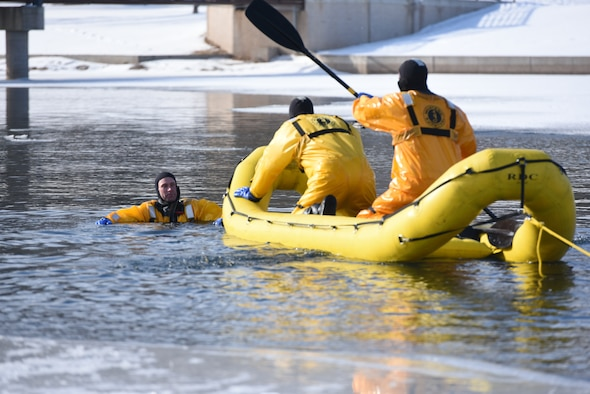 "Airmen from the 28th Civil Engineer Squadron Fire Protection Flight practice using a rapid deployment craft in order to perform ""rescues"" during training at Canyon Lake in Rapid City, S.D., Feb. 12, 2019. Although a team of two is on thecraft, there's still a four-to five-man team on the ice nearby ready to pull them back to safety. (U.S. Air Force photo by Senior Airman Michella Stowers)"