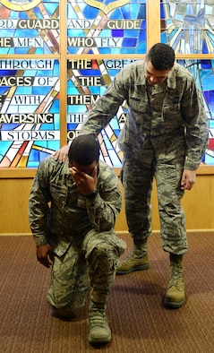 U.S. Air Force Airman 1st Class Dmarko Brown 55th Wing chaplain assistant, kneels down for a photo while U.S. Air Force Master Sgt. David Burgos, 55th Wing non-commission officer in charge chapel operations, places his hand on browns shoulder February 15, 2019, inside the Strategic Air Command Memorial chapel at Offutt Air Force Base, Nebraska.