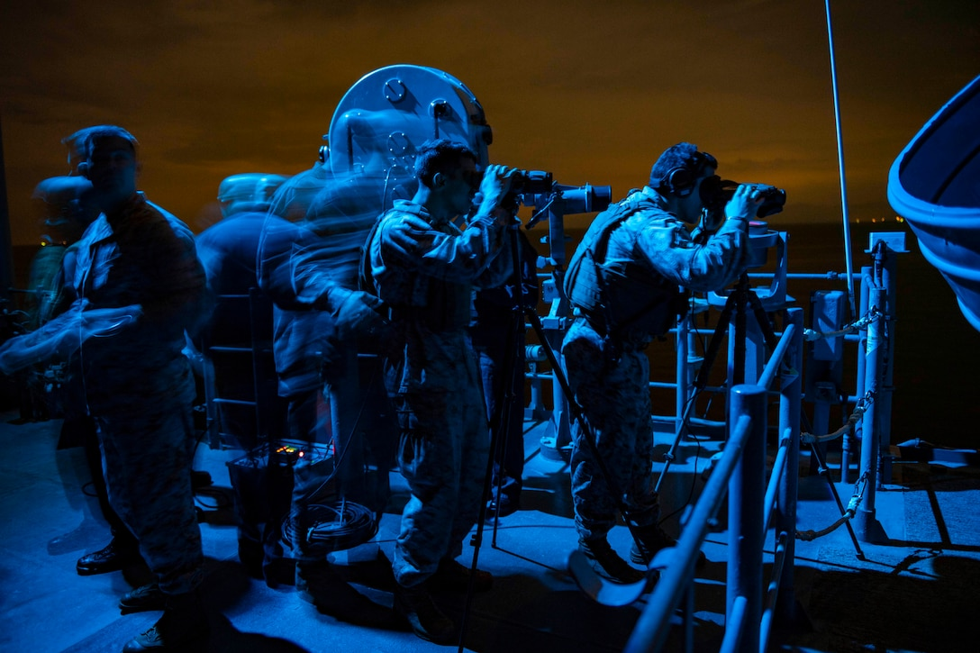 Service members, illuminated by blue light, stand watch on ship's deck, some with binoculars.