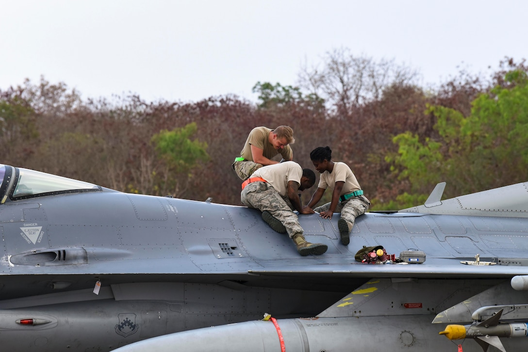Three airmen sit atop a jet while  performing maintenance.