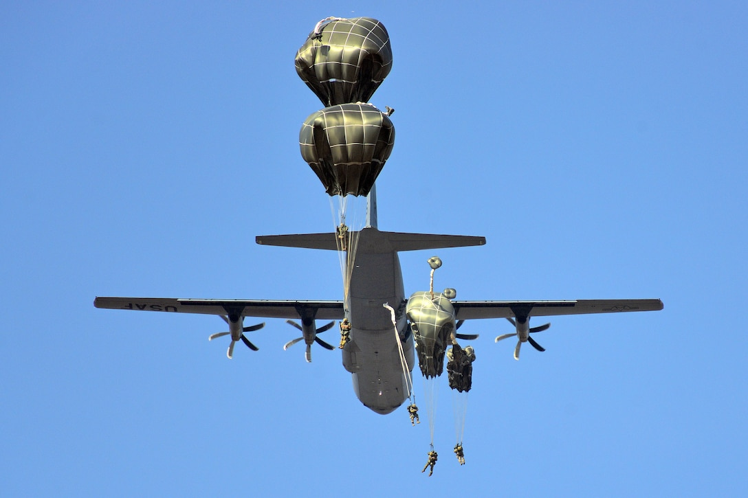 Parachutists jump from a large military aircraft against a blue sky.