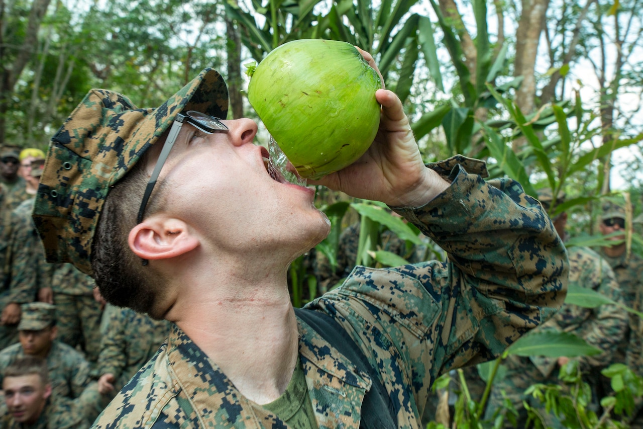 A Marine, shown in profile, drinks from a coconut he holds above his mouth.