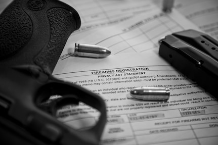 A 9 mm pistol and ammunition sit on top of an AF Form 1314 Firearms Registration form and a DD Form 2760 Qualification to Possess Firearms or Ammunitions form in this Air Force file photo.